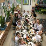 Grupa dzieci siedzących przy stole wigilijnym wraz z Paniami.