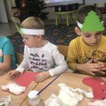 Troje dzieci siedzących przy stolikach i wykonujących prace plastyczne - mikołajkowe skarpety na prezenty