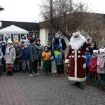 Grupa dzieci stojących przed budynkiem przedszkola z trzema Paniami. Przez nimi stoi Mikołaj.