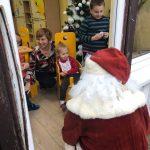 Mikołaj zaglądający przez okno do sali, w której znajduje się dziewczynka siedząca na krześle. Za nią kuca Pani, obok niej stoi chłopiec.