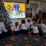 Grupa dzieci wraz z dwoma Paniami siedzących na dywanie i oglądających bajkę na tablicy interaktywnej.
