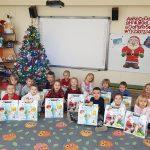 Grupa dzieci siedzących na dywanie, trzymających w rękach świąteczne prezenty.
