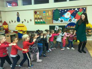 Dzieci stojące na dywanie jedno za drugim i trzymające się za ramiona. Na początku rzędu znajduje się Pani.