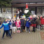 Grupa dzieci stojących przed budynkiem przedszkola. Za nimi stoją dwie Panie.