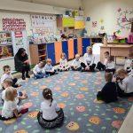 Dzieci siedzące w kole na dywanie. Pomiędzy nimi dwie Panie.