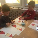Dwoje dzieci siedzących przy stoliku i wykonujących prace plastyczne przedstawiające Mikołaje.