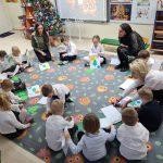 Grupa dzieci siedzących w kole na dywanie i wykonujących świąteczne zadania. Przed każdym dzieckiem znajduje się koperta z ilustracją choinki i bombki. Pomiędzy dziećmi znajdują się trzy Panie.
