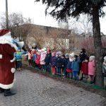 Grupa dzieci stojących w ogrodzie przedszkolnym wraz z dwoma Paniami. Przed nimi stoi Mikołaj.