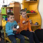 Dwóch chłopców siedzących na krzesłach. Chłopiec w niebieskiej bluzce trzyma w ręku latarkę, natomiast chłopiec w pomarańczowej bluzce trzyma w ręku młotek.