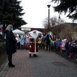 Grupy dzieci stojących przed budynkiem przedszkola wraz z Paniami. Przed nimi stoi Mikołaj. Z lewej strony stoi Pani Dyrektor.