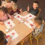 Dzieci siedzące przy stolikach i wykonujące prace plastyczne przedstawiające Mikołaje.