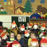 Grupa dzieci stojących na dywanie i trzymających w rękach prace plastyczne przedstawiające Mikołaje.