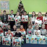 Grupa dzieci trzymających w rękach świąteczne prezenty.