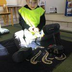 Chłopiec siedzący na dywanie i trzymający w ręku młotek. Przed nim znajduje się zapalona latarka.