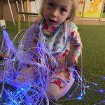 dziewczynka siedzi na dywanie i bawi się światłowodami w kolorze niebieskim.