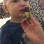 Chłopiec wącha buteleczkę z olejkiem zapachowym .