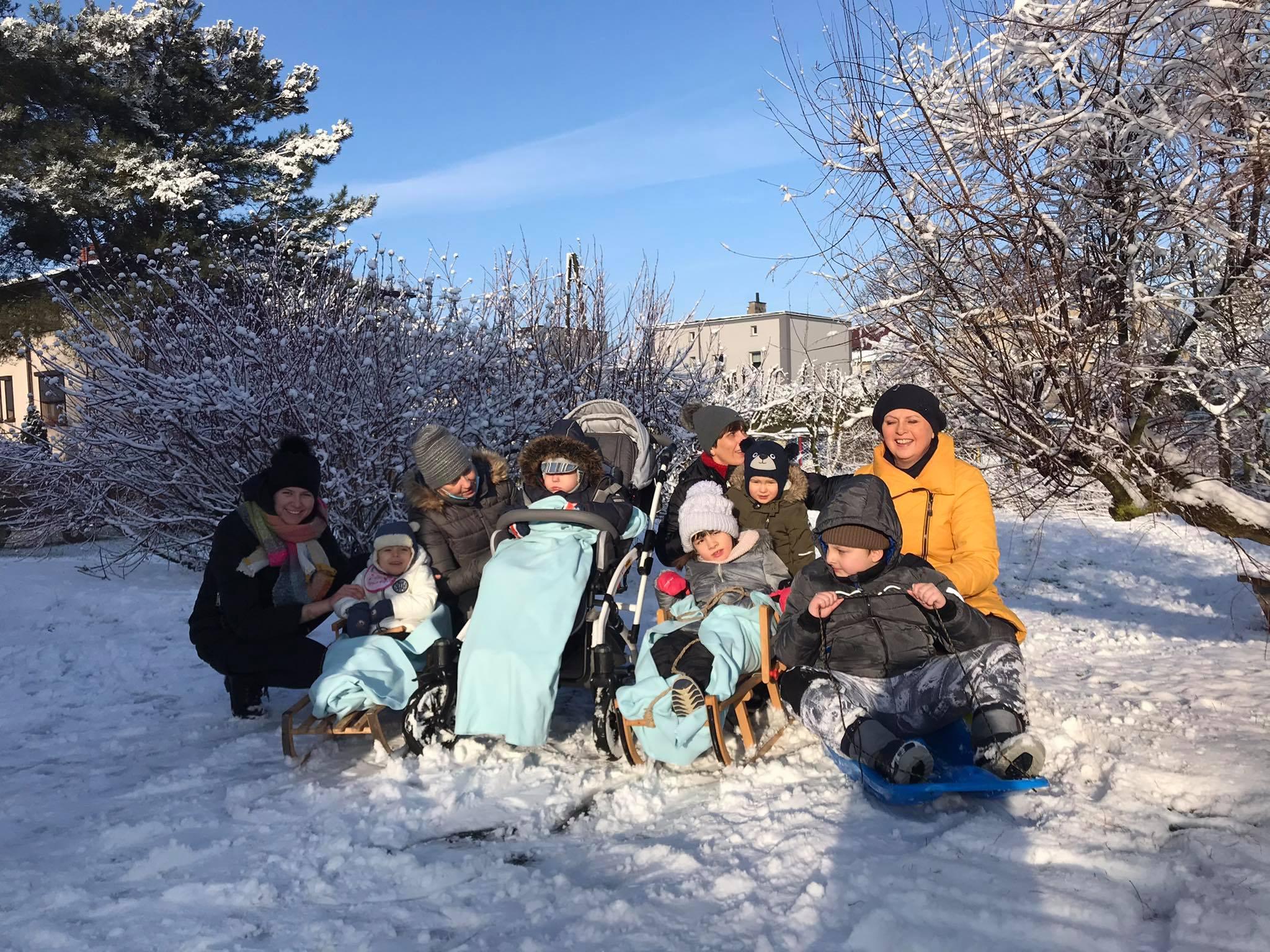 Grupa dzieci i Pań na dworze w krajobrazie zimowym. Kolkiro dzieci siedzi na sankach.