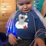 chłopiec siedzi na dywanie i bawi się światłowodami w kolorze niebieskim.