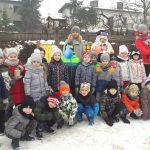 Duza grupa dzieci stoi na dworze z Paniami. Jest dużo śniegu.