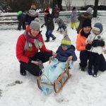 Dziecko siedzi na sankach, które trzyma Pani . Obok stoi dziewczynka trzymana przez Panią. Za nimi grupa dzieci rzuca się snieżkami. Na dworze jest dużo śniegu.