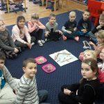 Dzieci siedzą na dywanie w kole. Na środku leży kartka z narysowanym karmnikiem i dwie tace z ziarnami.