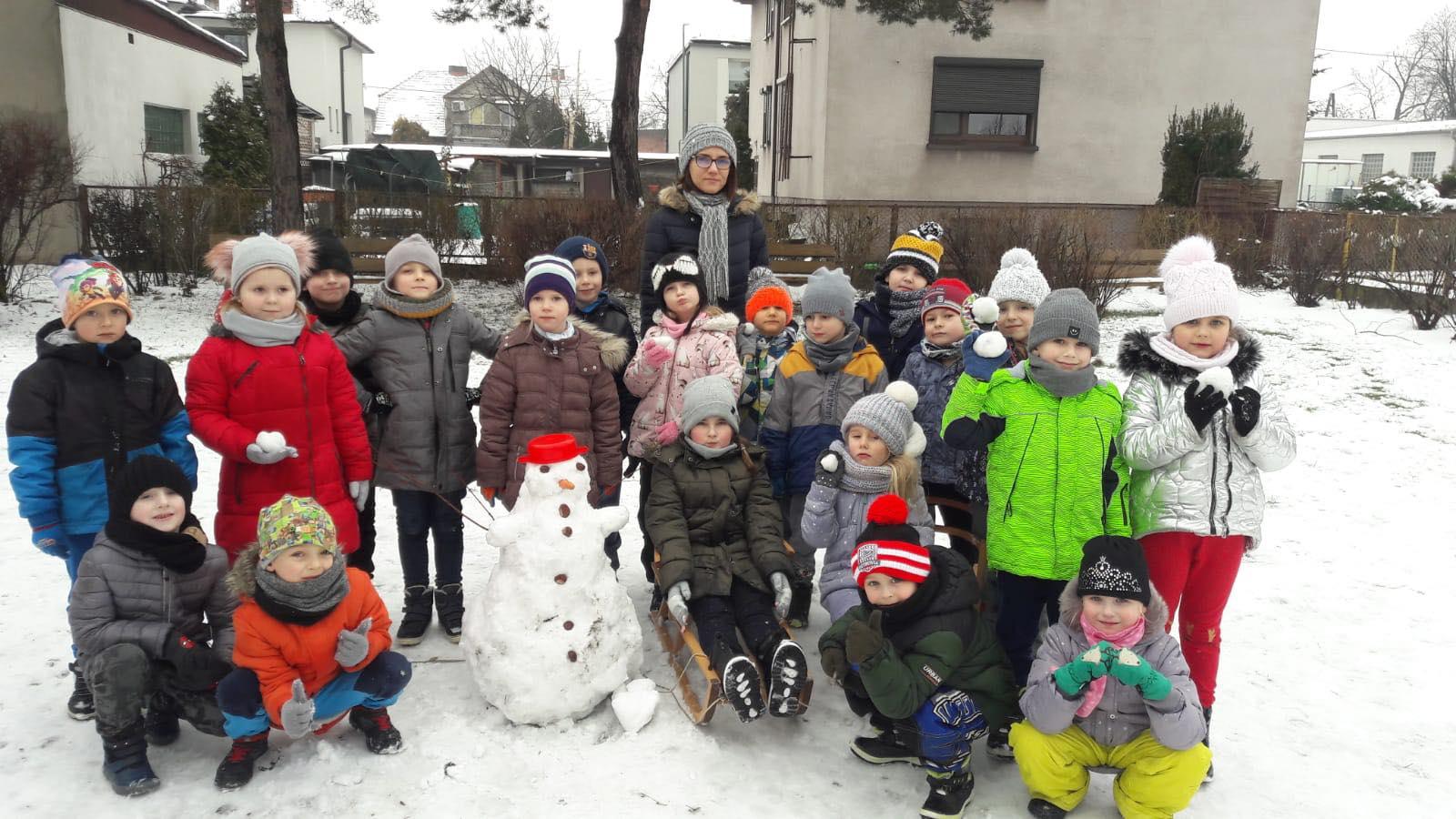 Grupa dzieci stoi na dworze z ulepionym bałwnem. Na dworze jest dużo śniegi.
