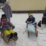 Dwoje dzieci siedzi na sankach. Za nimi stoi dziewczynka ze śnieżką w ręce.
