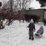 Dziewczynka trzyma sznurek od sanek, na których siedzi inna dziewczynka. Obok stoi chłopiec z dużą kulką śniegu.