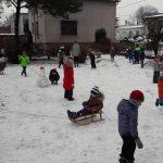 Grupa dzieci na placu przedszkolnym. Jedne stoją, inne pochylają się po śnieg. Na środku siedzi dziecko na sankach. Jest dużo śniegu.