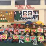 Grupa dzieci pozująca do zdjęcia w dwóch rzędach w sali przedszkolnej. Każde dziecko trzyma w rękach laurkę dla babci i dziadka.
