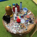 Na stoliku widać: szpulki nici, guziki, nożyczki, taśemki, szpilki, centymetr, kawałek materiału.