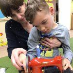 Chłopiec siedzi na kolanach Pani. Przed nimi stoi na stoliku maszyna do szycia, na którą się patrzą i dotykają jej.