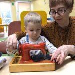 Chłopiec siedzi na krześle koło nauczycielki. Przed nimi stoi na stoliku maszyna do szycia, na którą się patrzą i dotykają jej.