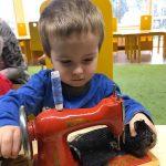 Chłopiec siedzi na krześle. . Przed nim stoi na stoliku maszyna do szycia, na którą się patrzą i dotyka jaj.