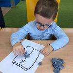 Chłopiec siedzi przy stoilku. Przed sobą na kontur spodni, który wykleja pociętym na kawałki materiałem.