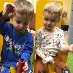 dwóch chłopców siedzi na krzesłach. W rękach trzymają szpulki nici.