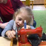 Dziewczynka siedzi na kolanach Pani. Przed nimi stoi na stoliku maszyna do szycia, na którą się patrzą i dotykają jej.