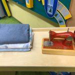 Na stoliku stoi stara maszyna na szycia i złożone w kostkę materiały różnego koloru.