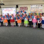 Grupa dzieci odświętnie ubranych, stojących w jednym rzędzie w sali przedszkolnej, mających założone na rękach kolorowe kwiatki.