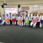 Grupa dzieci odświętnie ubranych i trzymających w rękach białe, materiałowe chustki.