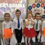 Sześcioro dzieci odświętnie ubranych, stojących w sali przedszkolnej w jednym rzędzie i trzymających w rękach białe, materiałowe chustki.