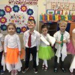 Sześcioro dzieci stojących w jednym rzędzie w sali przedszkolnej, odświętnie ubranych i trzymających w rękach białe, materiałowe chustki.