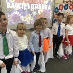 Ośmioro dzieci odświętnie ubranych, stojących w sali przedszkolnej w jednym rzędzie i trzymających w rękach białe, materiałowe chustki.