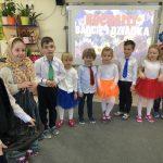 Dziesięcioro dzieci odświętnie ubranych, stojących w półkolu w sali przedszkolnej. Po lewej stronie stoi chłopiec przebrany za dziadka, trzymający w ręku kierownicę i dziewczynka przebrana za babcię.