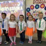 Siedmioro dzieci odświętnie ubranych, stojących w jednym rzędzie w sali przedszkolnej.