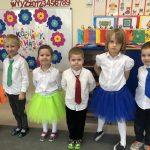 Sześcioro dzieci odświętnie ubranych, stojących w jednym rzędzie. w sali przedszkolnej.