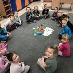 Grupa dzieci siedzących na dywanie w sali przedszkolnej. W środku znajduje się zestaw edukacyjny do programowania wraz z robotem.