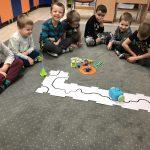 Siedmioro dzieci siedzących w półkolu na dywanie w sali przedszkolnej. Przed dziećmi znajduje się robocik poruszający sie po trasie ułożonej z biało-czarnych puzzli, plastikowe koło, wieża oraz kolorowe kostki.