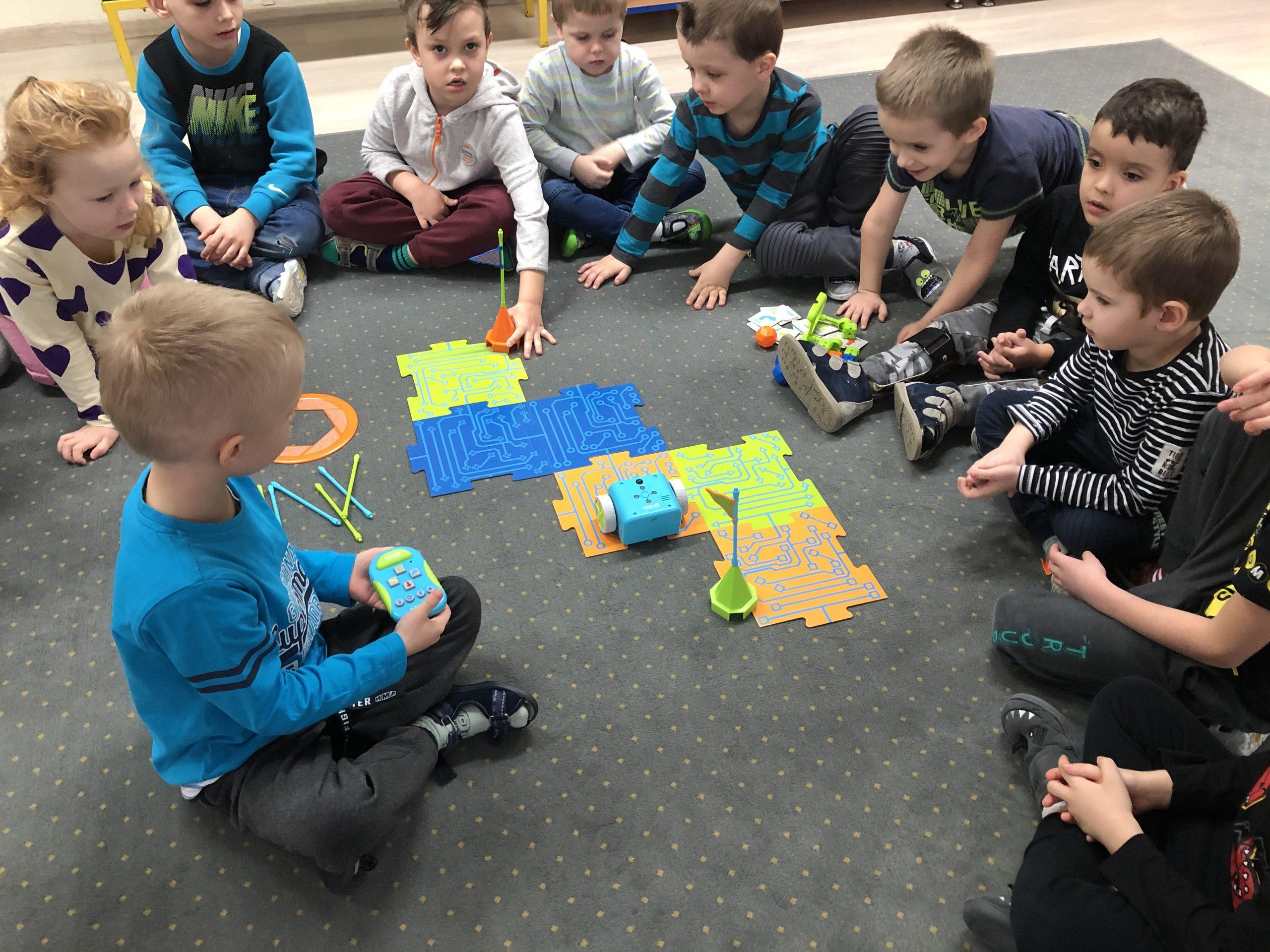 Grupa dzieci siedzących w kole na dywanie. W środku siedzi chłopiec trzymający w ręku pilota. Na dywanie znajduje się robot, który porusza się po wyznaczonej trasie.