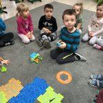 Siedmioro dzieci siedzących na dywanie w sali przedszkolnej. Jeden chłopiec siedzi przed pozostałymi dziećmi i trzyma w rękach pilota. Przed chłopcem znajduje się robocik, plastikowe koło, wieża oraz trsa ułożona z kolorowych puzzli.